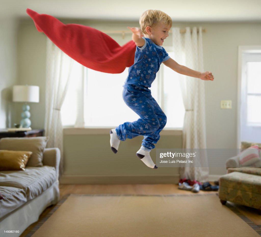 Caucasian boy in superhero costume jumping through the air