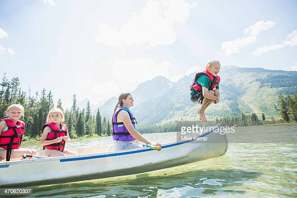 Caucasian boy jumping from canoe into lake