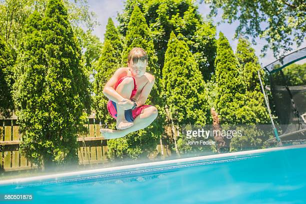Caucasian boy jumping into swimming pool