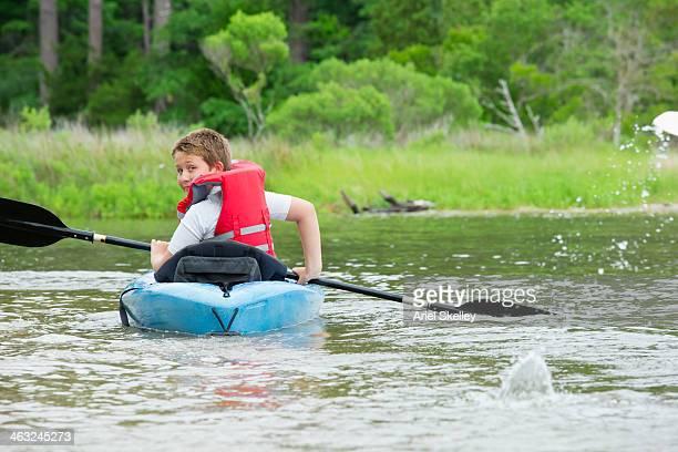 Caucasian boy kayaking in river