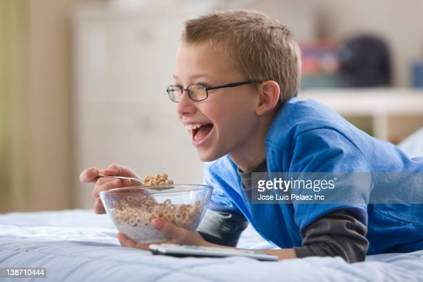 Caucasian boy laying on bed eating cereal