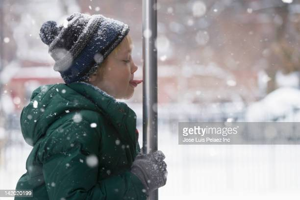 Caucasian boy licking metal pole in the snow