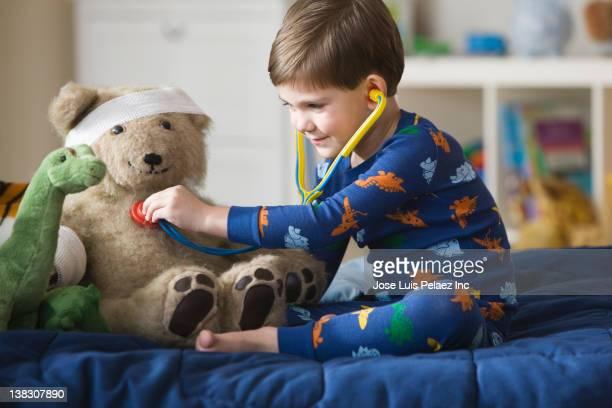 Caucasian boy listening to teddy bear's heartbeat with stethoscope