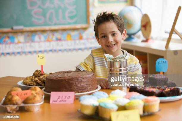Caucasian boy looking at baked goods for sale