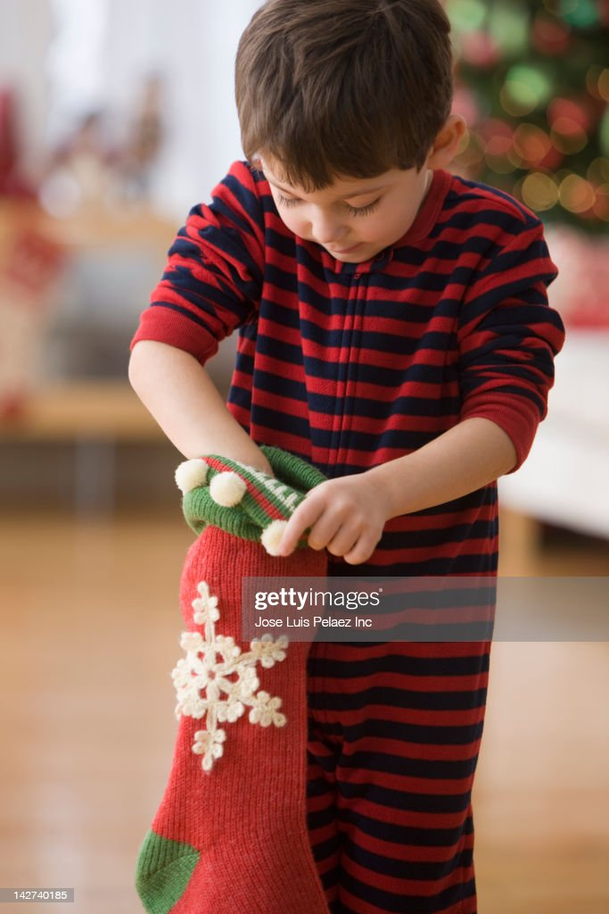 Caucasian boy looking in Christmas stocking