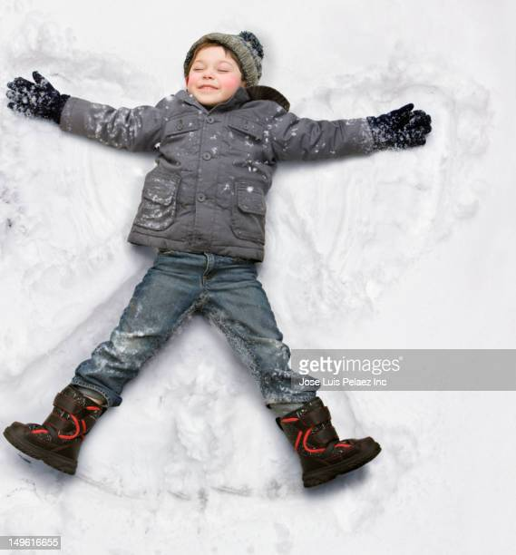 Caucasian boy making snow angel