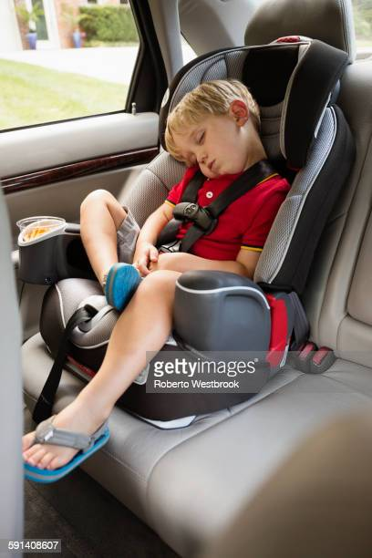 Caucasian boy napping in car seat