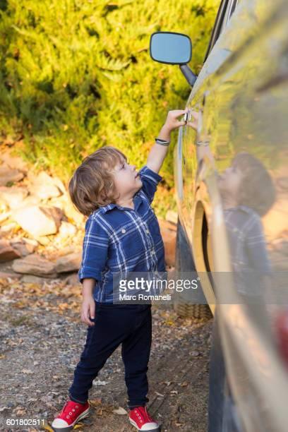 Caucasian boy opening car door