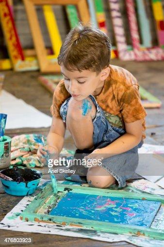 Caucasian boy painting in studio