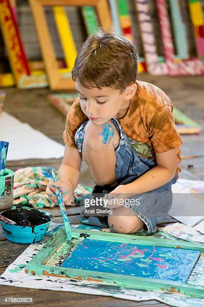 Caucasian boy painting in studio