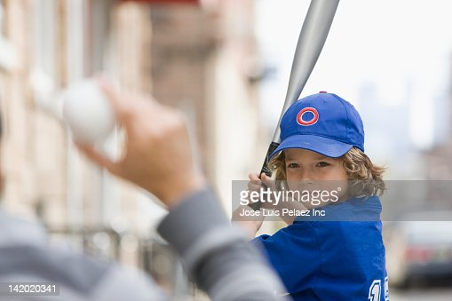 Caucasian boy playing baseball with father : Stock Photo