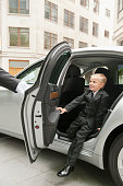 Caucasian boy playing businessman exiting car