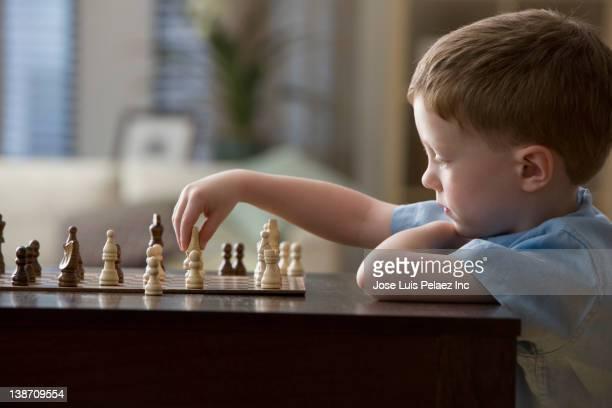 Caucasian boy playing chess