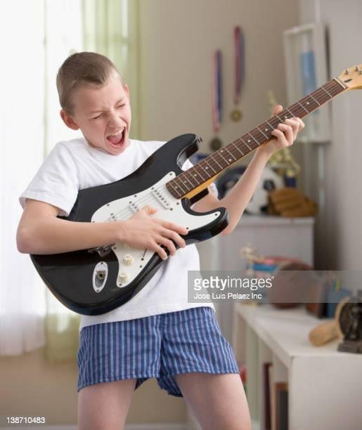 Caucasian boy playing guitar