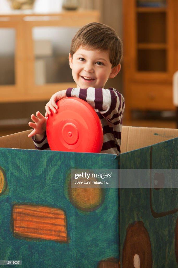 Caucasian boy playing in box : Stock Photo