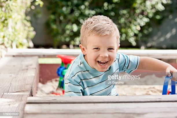 Caucasian boy playing in sandbox