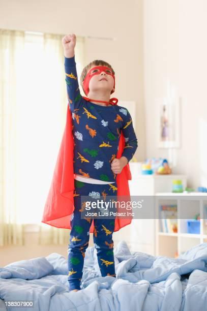 Caucasian boy playing in superhero costume