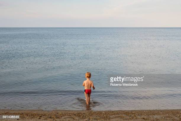 Caucasian boy playing on beach