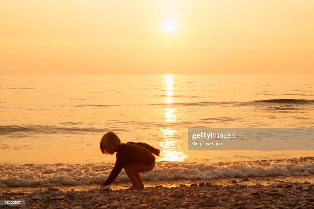 Caucasian boy playing on rocky beach at sunset