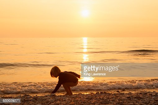 Caucasian boy playing on rocky beach at sunset