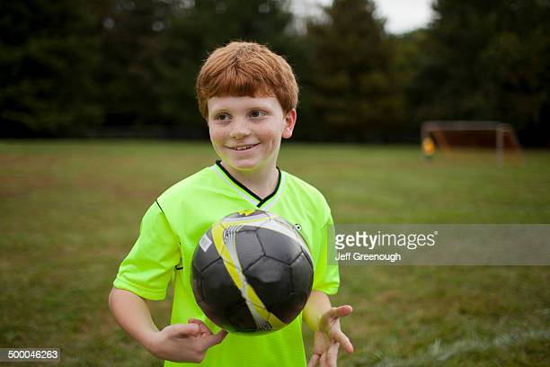 Caucasian boy playing soccer on field