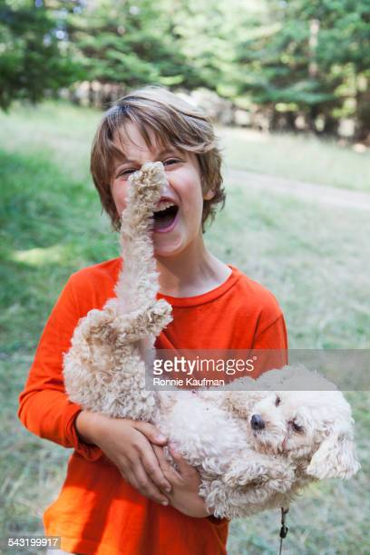 Caucasian boy playing with puppy outdoors