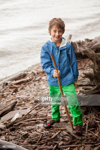 Caucasian boy playing with sticks by river
