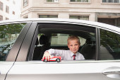 Caucasian boy playing with toy car in back seat