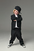 Caucasian boy posing in oversized suit