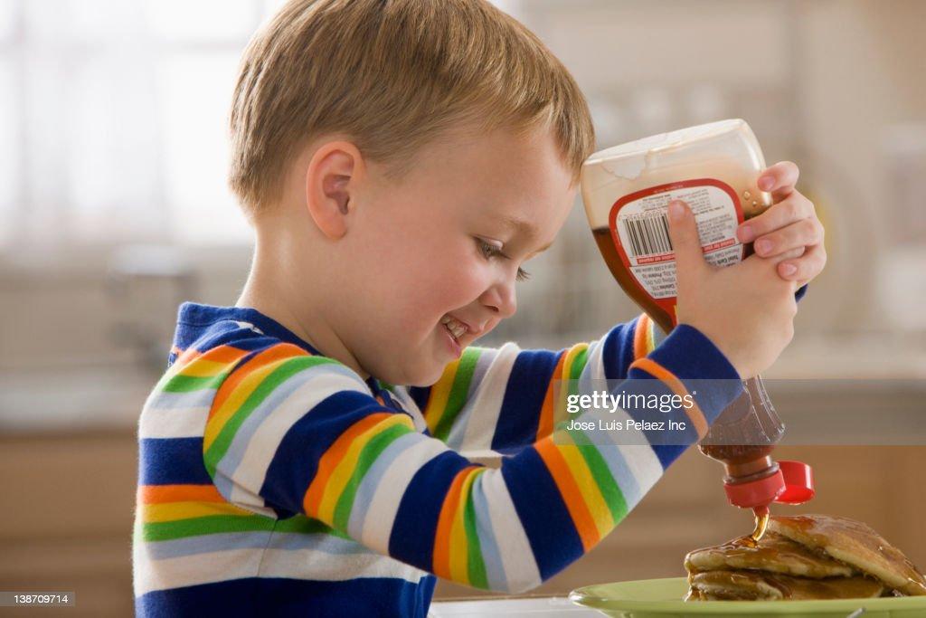 Caucasian boy pouring syrup on pancakes : Stock Photo