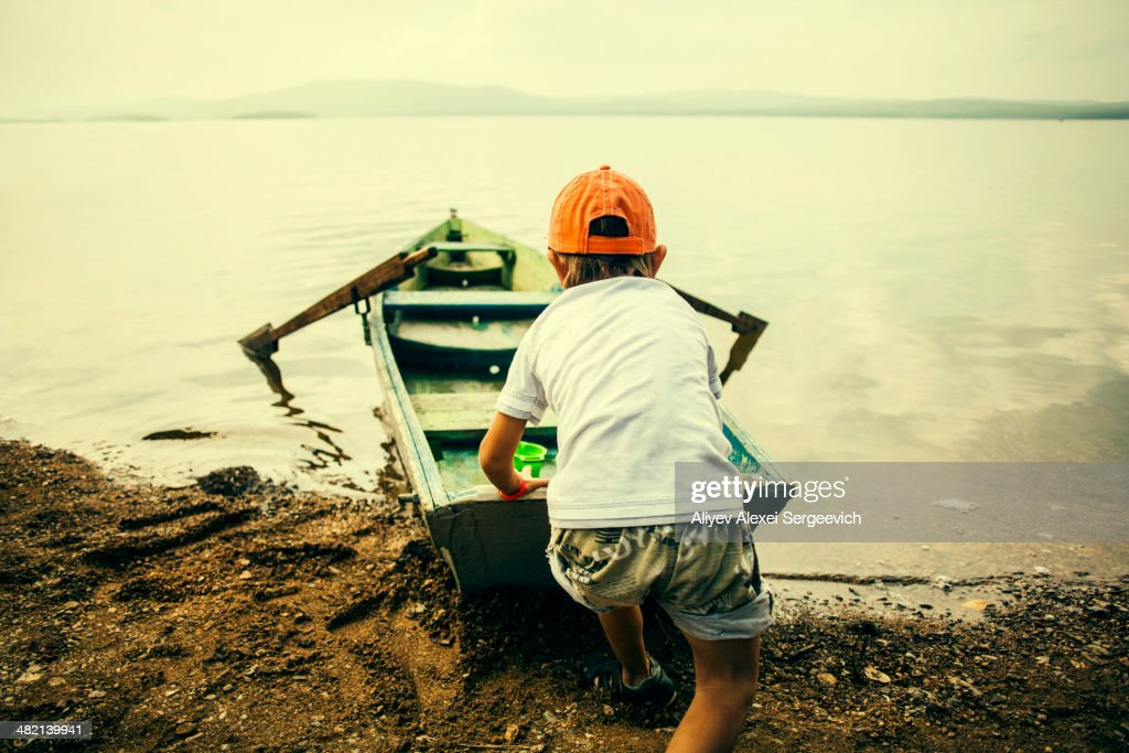 Caucasian boy pushing boat into still lake