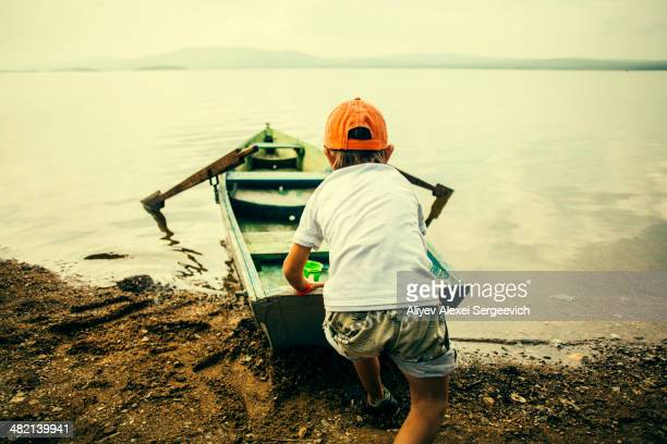 Caucasian boy pushing boat into still lake