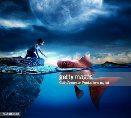 Caucasian boy reaching for oversized goldfish in ocean