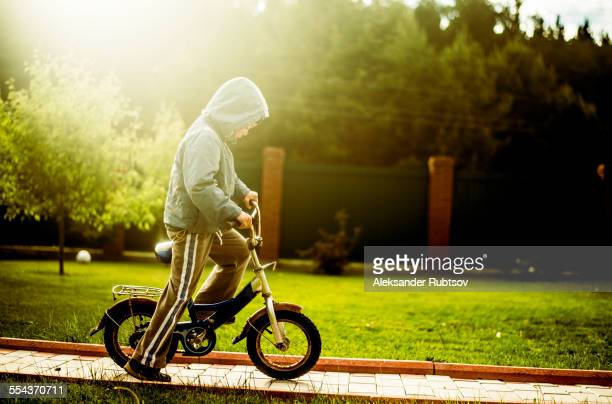 Caucasian boy riding bicycle in backyard