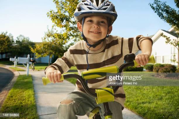 Caucasian boy riding bicycle on sidewalk