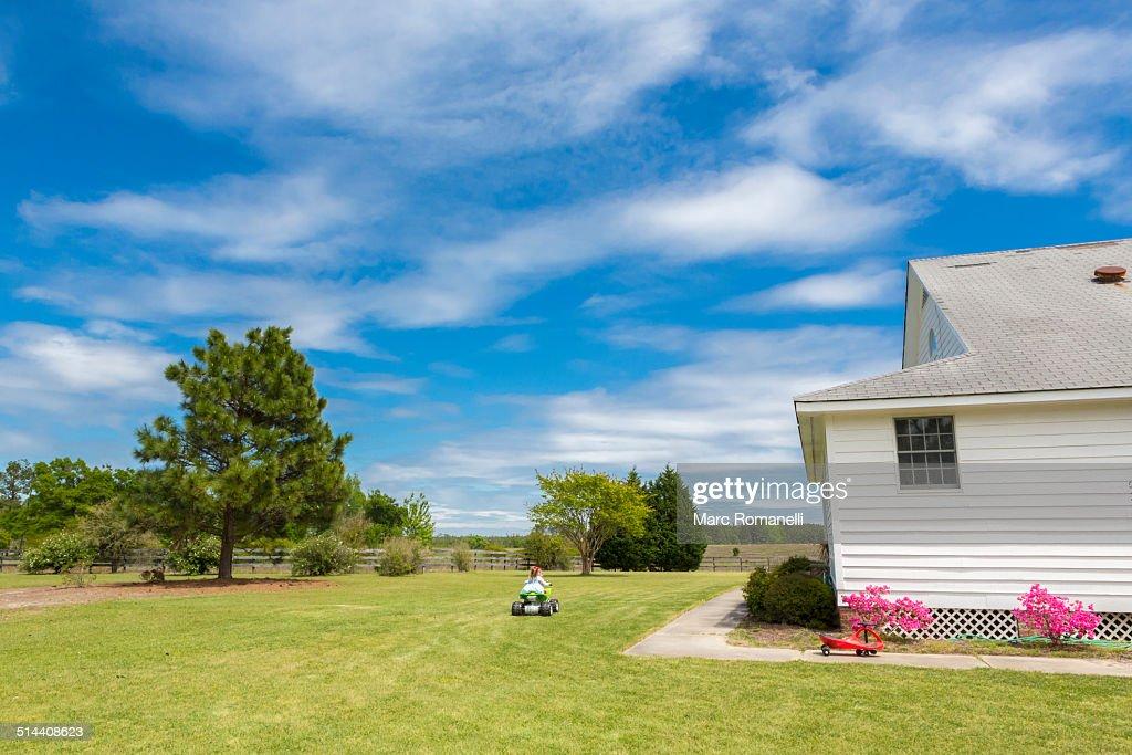 Caucasian boy riding four wheeler in backyard