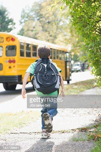 Caucasian boy running after school bus
