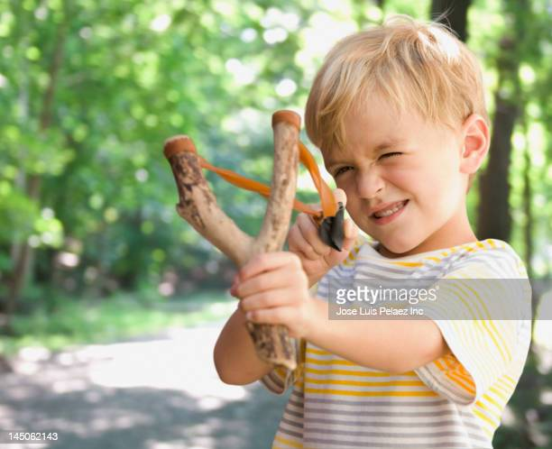 Caucasian boy shooting slingshot