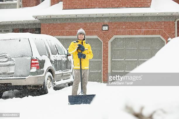 Caucasian boy shoveling driveway in snow