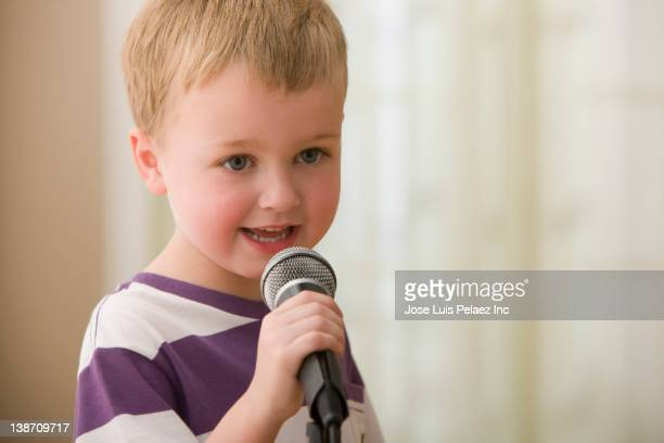 Caucasian boy singing into microphone