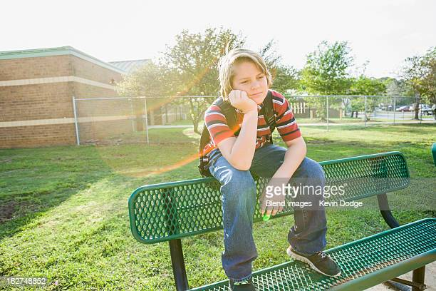 Caucasian boy sitting on bench