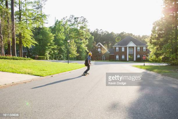 Caucasian boy skateboarding on road