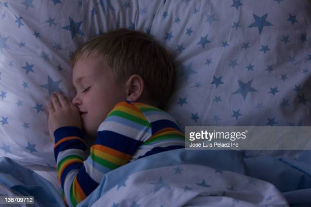 Caucasian boy sleeping in bed