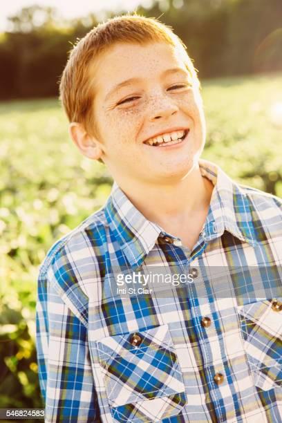 Caucasian boy smiling in crop field on farm