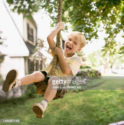 Caucasian boy swinging on rope swing