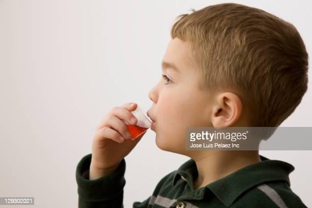 Caucasian boy taking cough medicine