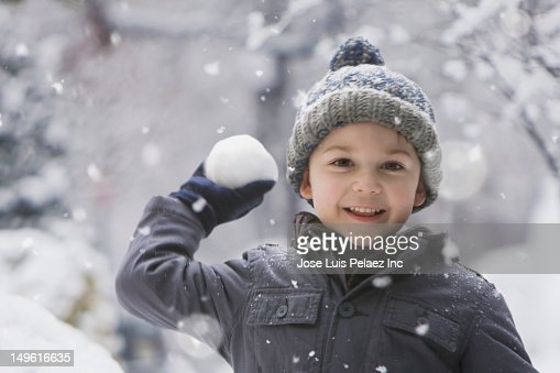 Caucasian boy throwing snowball