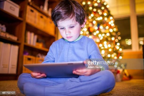 Caucasian boy using digital tablet by Christmas tree