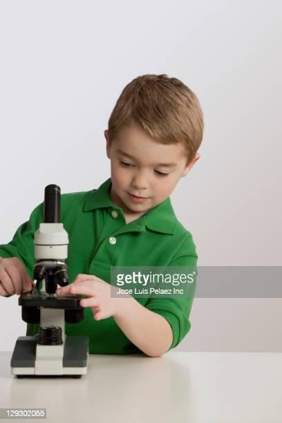 Caucasian boy using microscope