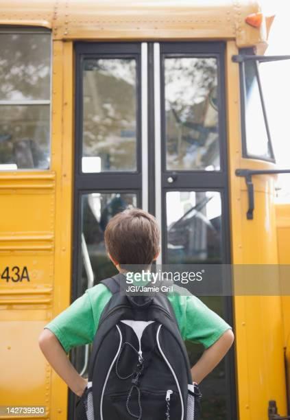 Caucasian boy waiting for school bus